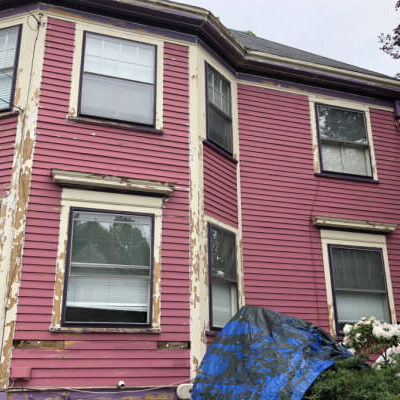 Before siding repair and exterior painting - Newton Painting Company - Pink two-story colonial home